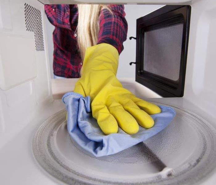 Hand wearing a protective glove wiping a microwave