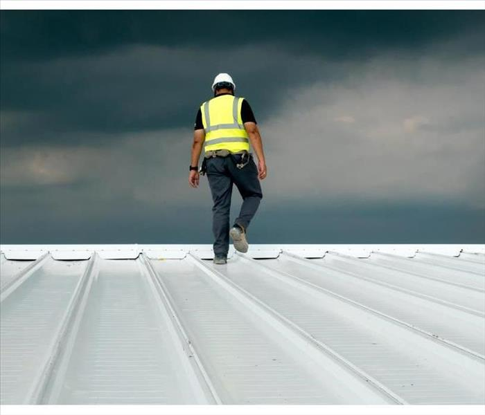 Construction engineer wearing safety uniform inspecting metal roofing work for roof industrial concept with copy space