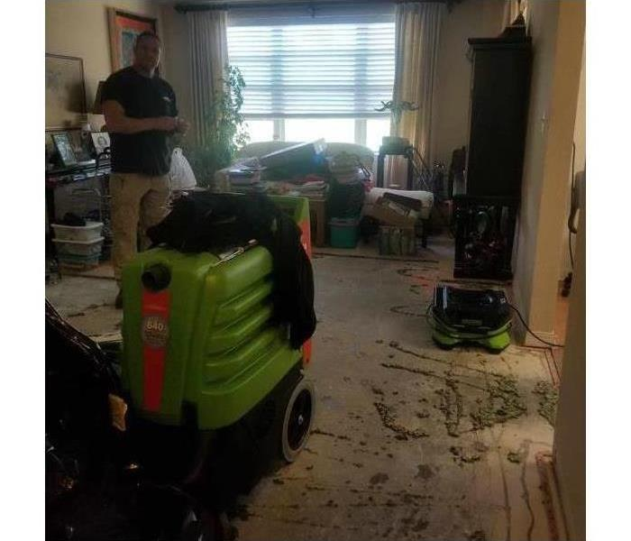Drying equipment on a living room a technician is presente, water damage caused on living room